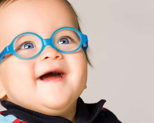 Child with glasses, close-up. On gray background.